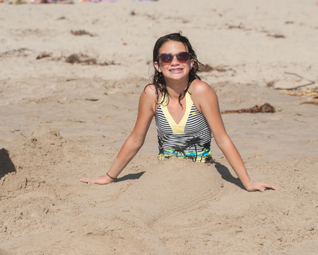 joins: Girl child joins sand art to appear as a mermaid