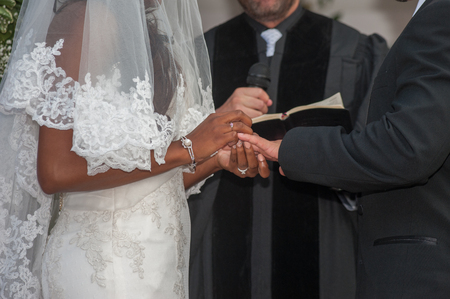 Bride places ring on grooms finger at alter.
