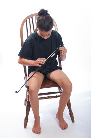 Girl child adding rosin to her bow strings