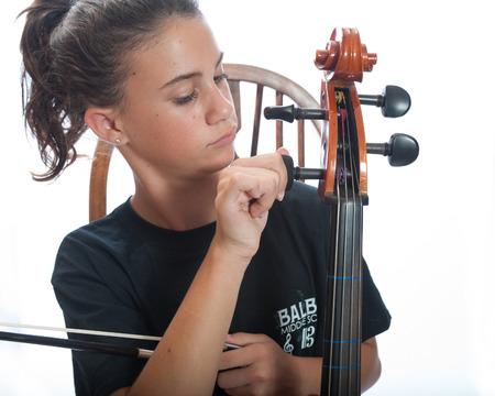 tunes: Girl child tunes her cello before practice. Stock Photo