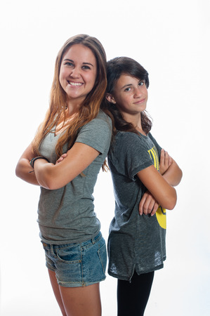 taller: Sisters standing back to back.