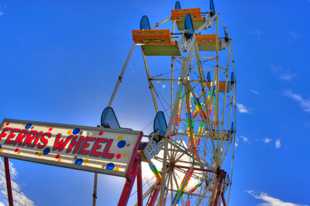 thrill: Ferris Wheel rides under blue sky Stock Photo