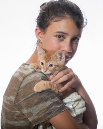 secure: Tabby kitten feeling secure on girls shoulder Stock Photo