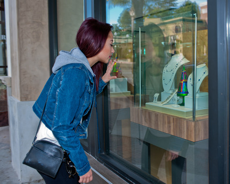 covet: Teenage woman looking at jewelry through the window.