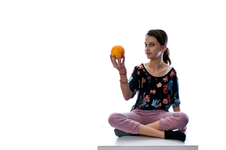 criss: Girl child sitting criss cross and holding an orange.