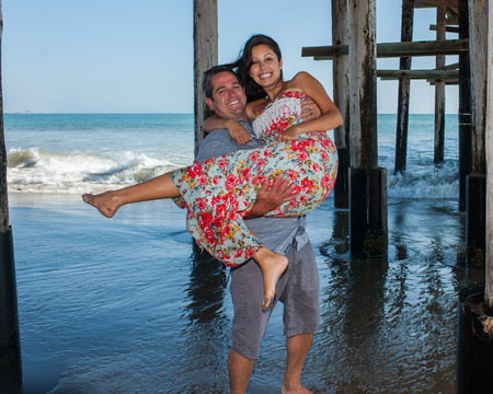 carrying: Man carrying his young wife out of the surf Stock Photo