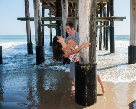 frolicking: Playful couple frolicking under the pier. Stock Photo