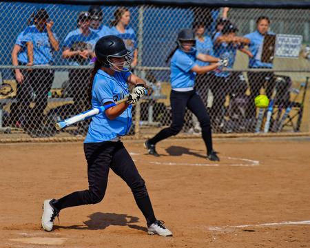 softball player: Female softball player swinging at a pitch.