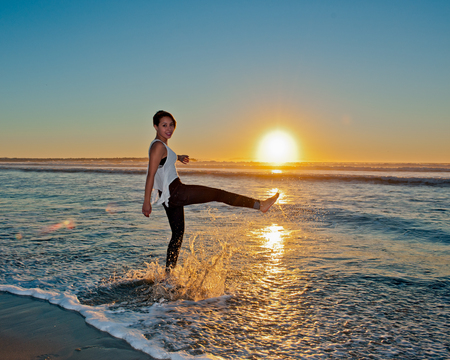 kicking: Female teen kicking up ocean water.