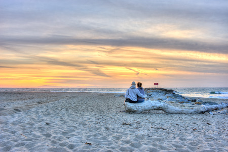 middle age couple: Middle age couple sitting on a log watching the sunset. Stock Photo