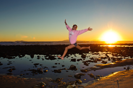 bounding: Girl child leaping over the tide pools. Stock Photo