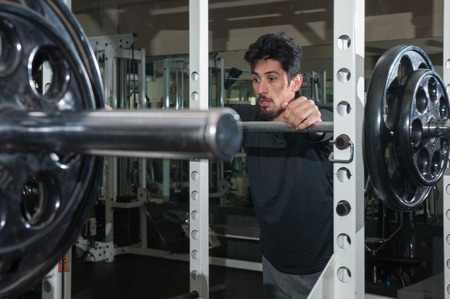 intervals: Male athlete resting between sets of squats. Stock Photo