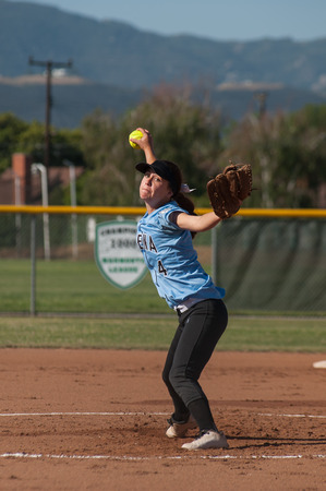 Female softball pitcher in her wind up.