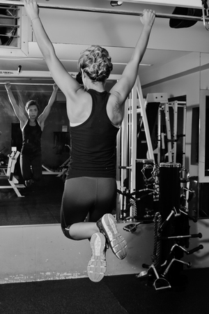 Female athlete hanging from a pull up bar. Stock Photo