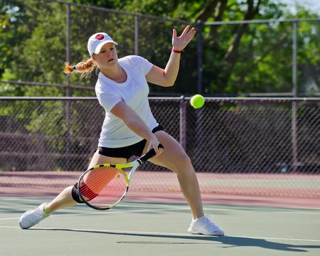 フォアハンド ボレーで続く女子テニス選手。