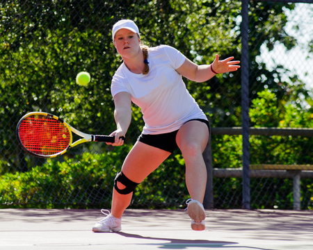 College female tennis player hitting a forehand volley.