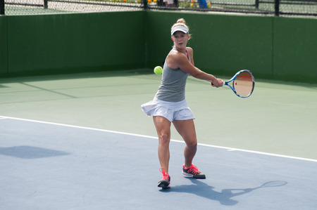 backhand: Female tennis player has ball lined up for a backhand.