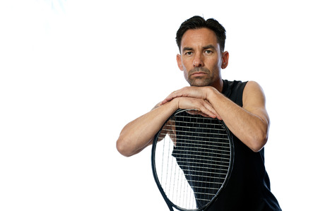 Middle age male tennis player has chin resting on racquet.