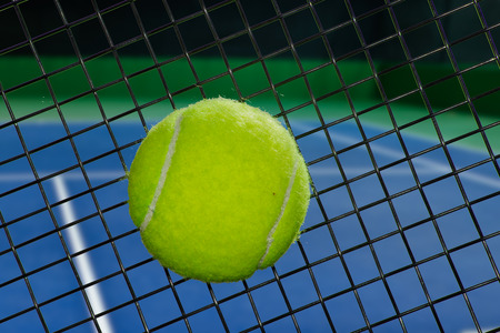 Tennis ball on the strings of a racquet.