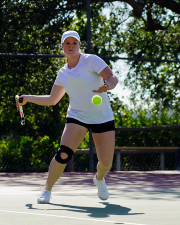 eye ball: College female tennis player has eye on the ball.