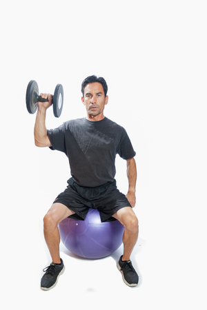 weighted: Middle age man sitting on stability ball wearing weighted vest.