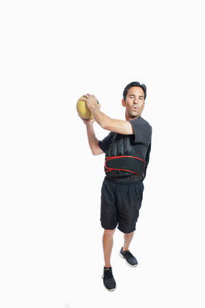 weighted: Middle age man with medicine ball wearing weighted vest.