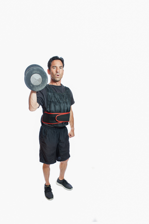 weighted: Middle age man lifting dumbbell wearing weighted vest.