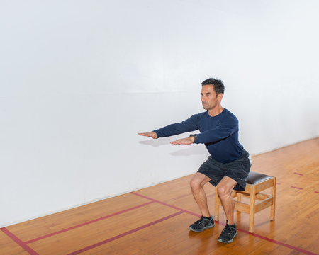 Middle age man demonstrating bench squat strength exercise at end position.