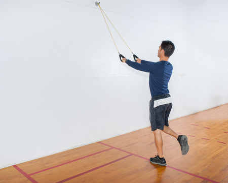 straight man: Middle age man demonstrating single leg straight pulldown strength exercise at start position.