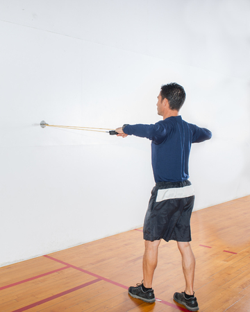 deltoid: Middle age man demonstrating rear deltoid strength exercise at end position.