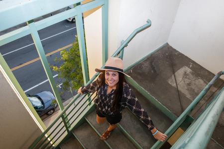 descending: Female teen descending parking structure stairs.