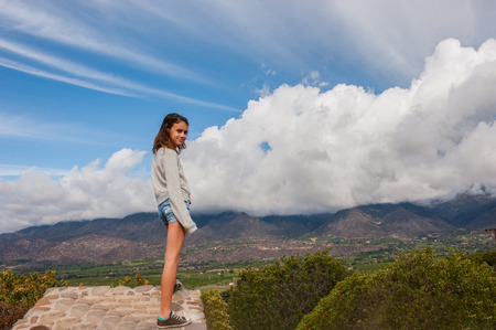 conquer: Female child posing against a windy, cloudy sky.
