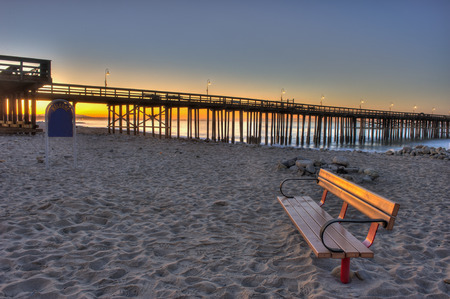 dawns: Bench at the beach with a view of the dawns glow.