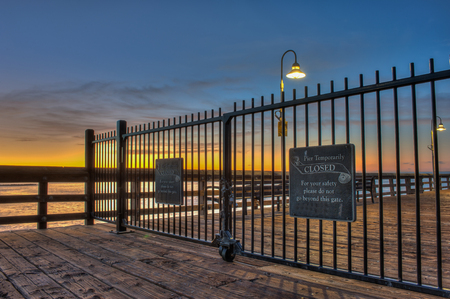 Low angle of locked iron gate blocking access to pier.