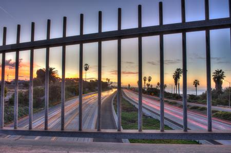 rejas de hierro: Tr�fico de la autopista muestra a trav�s de las barras de hierro.