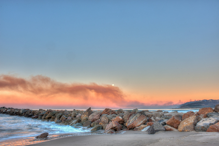 wafting: Smoke wafting across the horizon from the hillside fire.