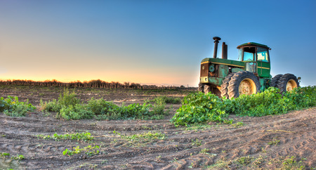 wider: Wider view of tractor on fallow field.