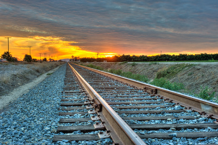detailed view: Detailed view of train tracks under cirrocumulus clouds. Stock Photo
