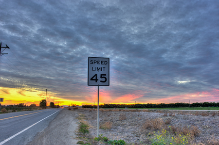 posted: Speed limit sign posted under cirrocumulus clouds. Stock Photo