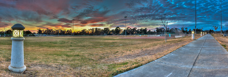 outfield: Softball field at sports park under setting sun in panoramic view.
