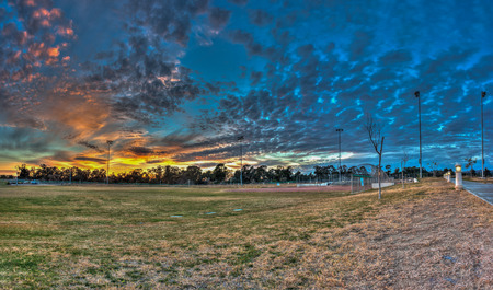 outfield: Softball field at sports park under cirrocumulus clouds in panoramic view. Stock Photo