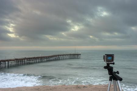 Caméra installée sur un trépied surplombant l'océan. Banque d'images - 52179201