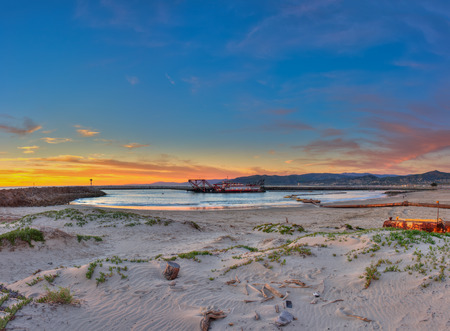 sand harbor: Panoramic view of dredge barge and pipeline in the Ventura harbor beyond the sand dunes. Stock Photo