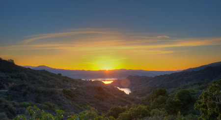 Panoramic view of sun just about to peek out over Lake Casitas. Imagens