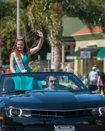 reigning: Teen pageant queen waving to crowd from convertible with her driver.