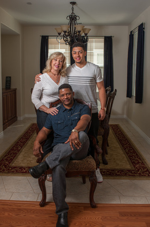 multiracial family: Wide view of handsome man seated with his multi-racial family.