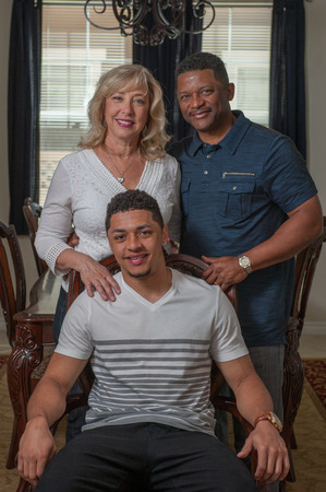 multiracial family: Closer view of handsome son seated with his multi-racial family. Stock Photo