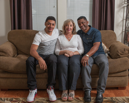 multiracial family: Multiracial family looking straight ahead seated on the couch. Stock Photo