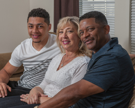 multiracial family: Tight view of multiracial family seated on the couch.