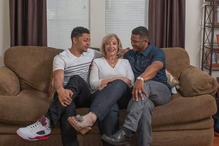 families together: Multiracial family looking at mom seated on the couch. Stock Photo
